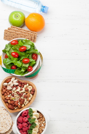 Healthy food and fitness concept. Salad, fruits, vegetables, nuts and cereal. Top view flat lay with copy space for your text Stock Photo