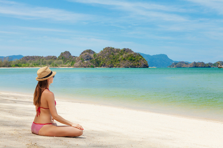 Young woman practice yoga on a beautiful tropical sea beach. Bright sand, blue sky and crystal sea. Tropical beach vacation concept. With copy space