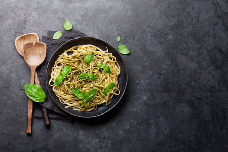 Spaghetti pasta with pesto sauce, parmesan cheese and fresh basil. Top view with copy space for your text Stock Photo