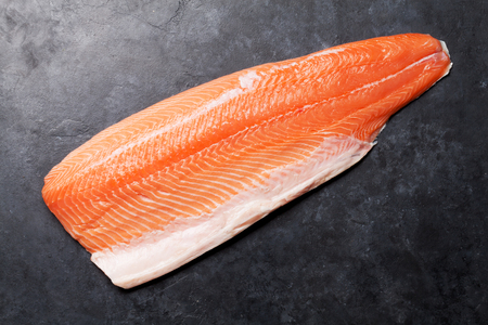 Raw salmon fish fillet for cooking on stone table. Top view flat lay with copy space Stock Photo
