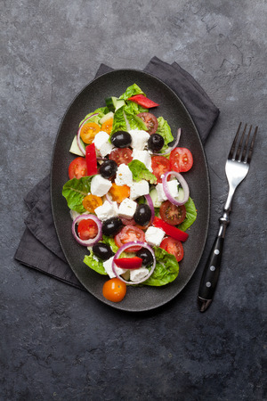 Greek salad with cucumber, tomato, pepper, lettuce, onion, feta cheese and olives, dressed with olive oil. Top view with space for your text Stock Photo