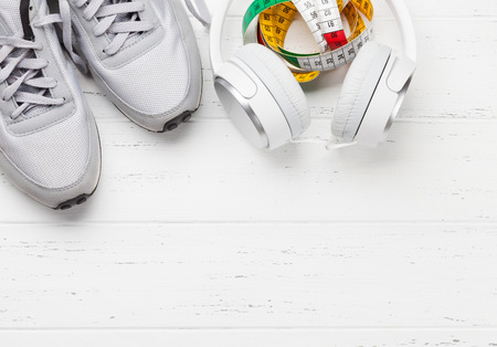 Fitness and healthy life concept. Sneakers, tape measure and headphones on wooden table. Top view with copy space for your text Stock Photo