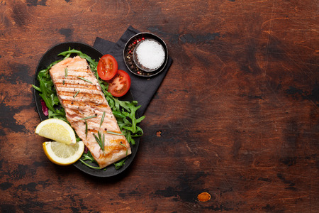 Grilled salmon fish fillet with salt, pepper and rosemary over salad leaves. On wooden table. Top view flat lay with copy space