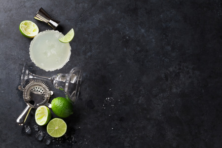 Margarita cocktail on dark stone table. Top view with space for your text