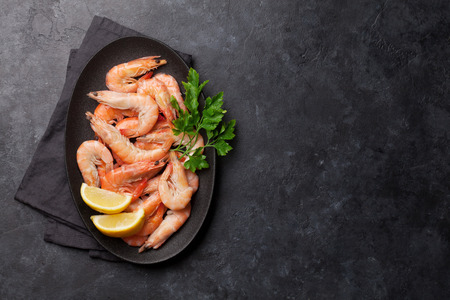 Steamed tiger shrimps with parsley and lemon. Top view with copy space for your text