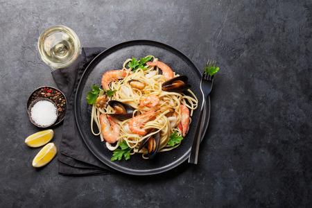 Spaghetti-Meeresfrüchte-Nudeln mit Muscheln und Garnelen. Weißweinglas. Draufsicht mit Kopienraum. Flach legen