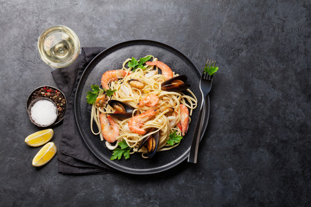 Spaghetti seafood pasta with clams and prawns. White wine glass. Top view with copy space. Flat lay