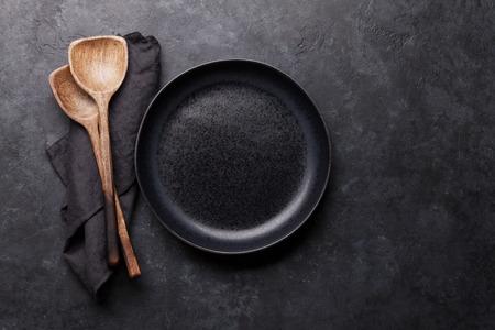 Kochen von hölzernen Utensilien und leerem Teller. Essen kochen Vorlagenkonzept. Draufsicht mit Kopienraum. Flach legen
