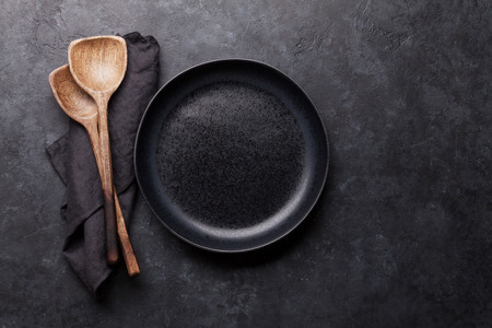 Cooking wooden utensils and empty plate. Food cooking template concept. Top view with copy space. Flat lay