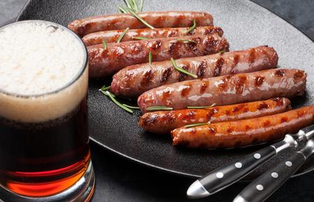 Gegrilde worstjes met rozemarijnkruiden en glas donker bier Stockfoto
