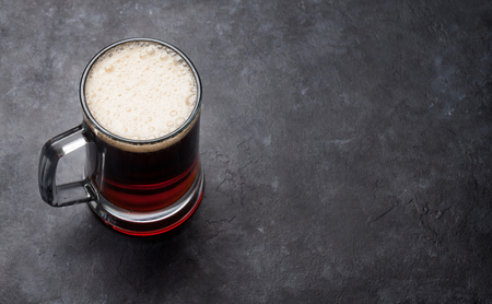 Glass of dark porter beer on stone table. With copy space