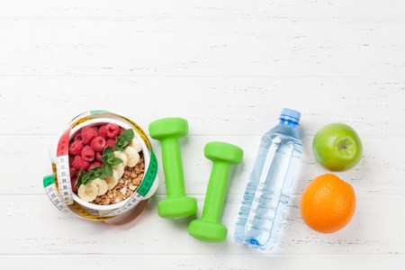 Healthy food and fitness concept. Breakfast cereal and sport equipment. Top view flat lay with notepad for your text