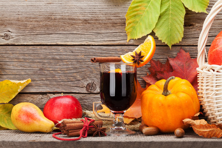 Autumn still life with mulled wine, pumpkins, apples, pears and colorful leaves in front of wooden wall. With space for your text Stockfoto