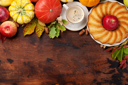 Autumn backdrop with pumpkins, apples, pears, cake, coffee and colorful leaves over wooden background. Top view with space for your text