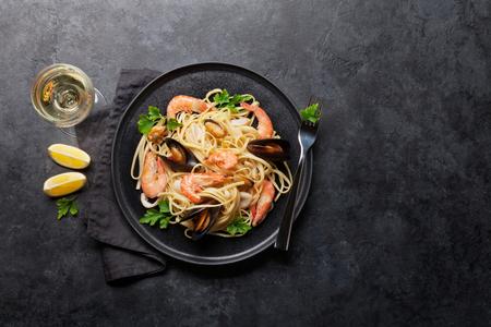 Pasta de espaguetis con mariscos con almejas y gambas. Copa de vino blanco. Vista superior con espacio de copia. Endecha plana