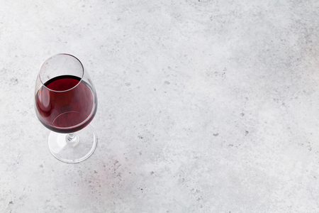 Red wine glass on stone backdrop. With space for your text