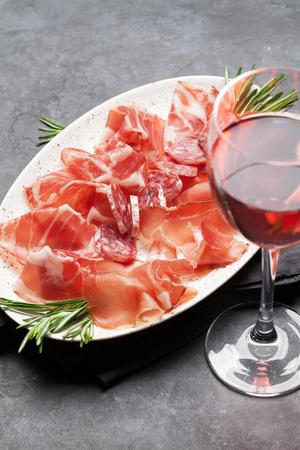 Traditional spanish jamon, prosciutto crudo, italian salami, parma ham. Antipasto plate and glass of wine Banco de Imagens