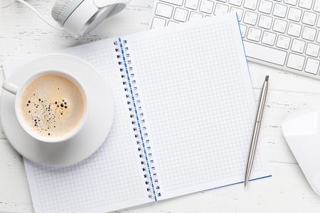 Office workplace table with notepad, coffee cup, supplies and pc. Flat lay. Top view with space for your goals Imagens