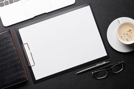 Office workplace table with blank paper page, coffee cup, supplies and laptop. Flat lay. Top view with space for your goals