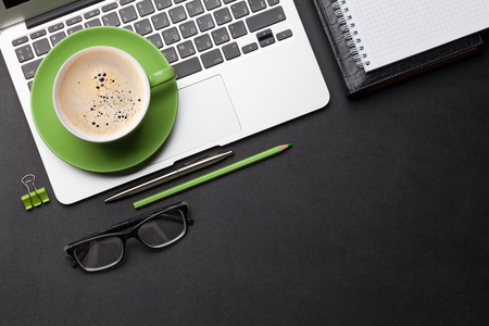 Office workplace table with coffee cup, supplies and computer Flat lay. Top view with space for your goals