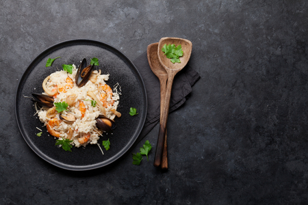 Delicious seafood risotto with shrimps, prawns, mussels. Dressed with parmesan cheese and parsley. Top view with copy space