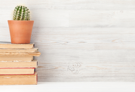 Home office workplace with stack of old books and cactus. Education concept. With copy space for your text