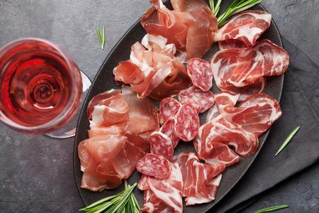 Traditioneller spanischer Jamon, Prosciutto Crudo, italienische Salami, Parmaschinken. Antipasti-Teller und ein Glas Wein. Draufsicht flach legen