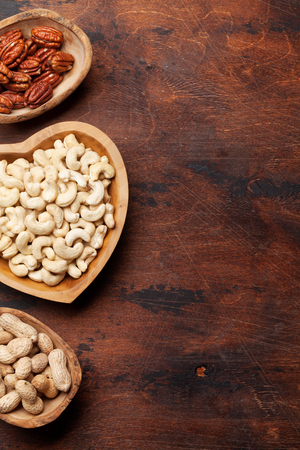 Various nuts selection: cashew, hazelnuts, chestnuts and pecans on wooden table. With space for your text