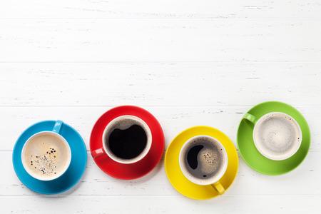 Kleurrijke koffiekopjes op witte houten tafel. Bovenaanzicht plat lag met kopieerruimte Stockfoto