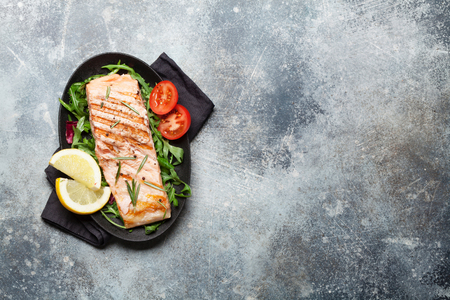 Grilled salmon fish fillet with salt, pepper and rosemary over salad leaves. On stone table. Top view flat lay with copy space