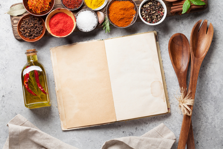 Set of various spices and herbs on stone background. Top view with cookbook for your recipe. Flat lay