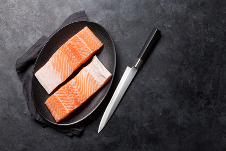 Raw salmon fish fillet for cooking on stone table. Top view flat lay with copy space 写真素材