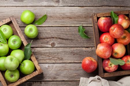 Pommes vertes et rouges mûres dans une boîte en bois. Vue de dessus avec espace pour votre texte