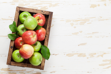 Ripe green and red apples on wooden table. Top view with space for your text