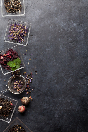 Set of different herbal and fruit dry teas in bowls on stone table. Top view flat lay with copy space Imagens