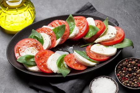 잘 익은 토마토, 신선한 정원 바질, 모짜렐라 치즈를 곁들인 맛있는 이탈리아 카프레제 샐러드