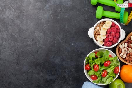 Concepto de fitness y alimentos saludables. Varias nueces, cereales, ensaladas y mancuernas. Vista superior plana con espacio de copia para su texto