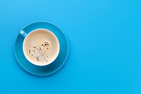 Blue coffee cup over blue background. Top view flat lay with copy space