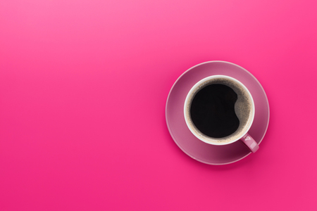 Tazza di caffè viola su sfondo viola. Vista dall'alto piatta con spazio di copia