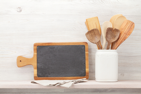 Set of various kitchen utensils. In front of wooden wall with chalkboard for your text Foto de archivo - 123911377