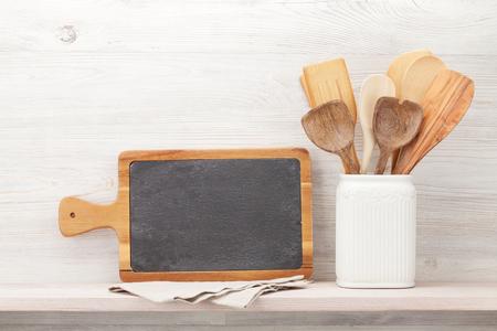 Zestaw różnych przyborów kuchennych. Przed drewnianą ścianą z tablicą na tekst