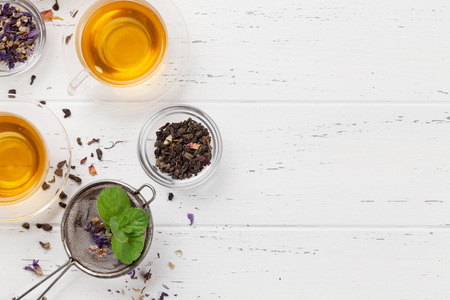 Different herbal and fruit dry teas and cups on wooden table.