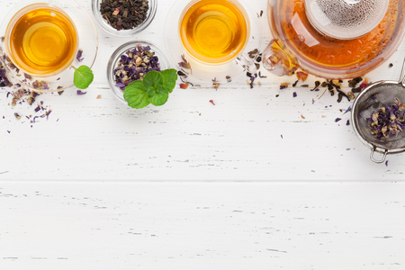Différents thés secs aux herbes et aux fruits, théière et tasses sur table en bois. Vue de dessus à plat avec espace de copie