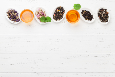 Different herbal and fruit dry teas and cups on wooden table. Top view flat lay with copy space