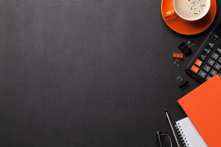 Office workplace table with coffee cup, supplies and calculator. Flat lay. Top view with space for your goals