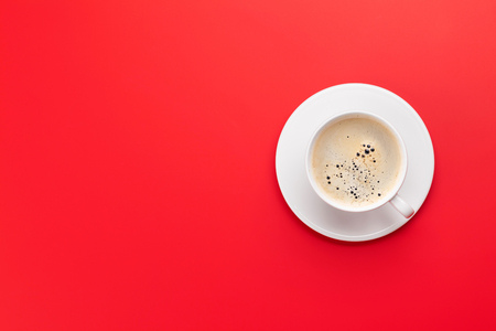 Coffee cup over red background. Top view flat lay with copy space