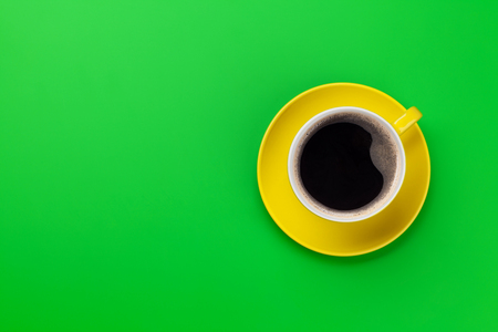 Yellow coffee cup over green background. Top view flat lay with copy space
