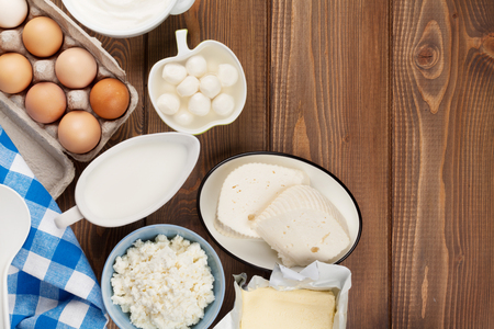 Prodotti lattiero-caseari sulla tavola di legno. Latte, formaggio, uova, ricotta e burro. Vista dall'alto con copia spazio