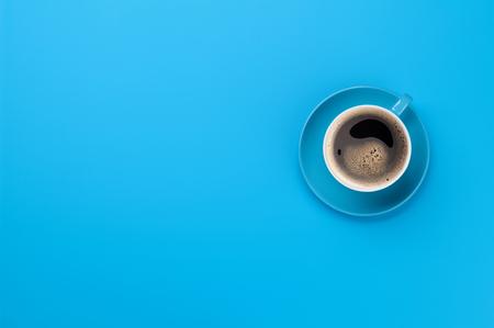 Blauwe koffiekopje over blauwe achtergrond. Bovenaanzicht plat lag met kopieerruimte Stockfoto