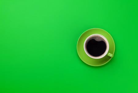Green coffee cup over green background. Top view flat lay with copy space 스톡 콘텐츠